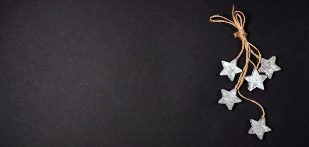 コピースペースで黒い背景の上面図の上に木製の星とロープでフラットレイの装飾