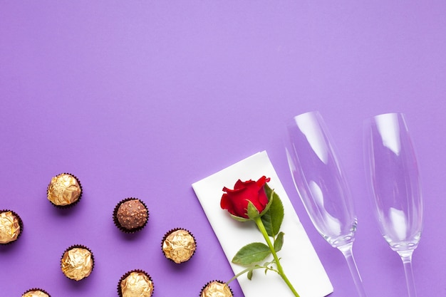 Flat lay decoration with chocolate balls and red rose