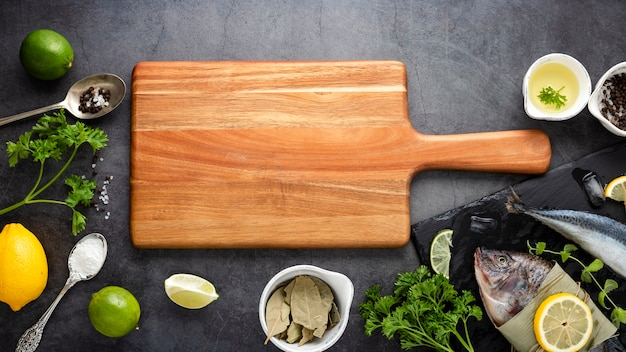 Flat lay decoration with cutting board and fish