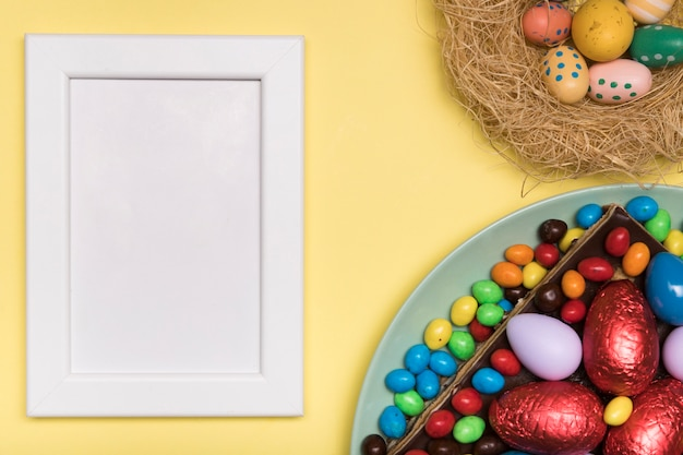 Flat lay decoration with easter food and white frame