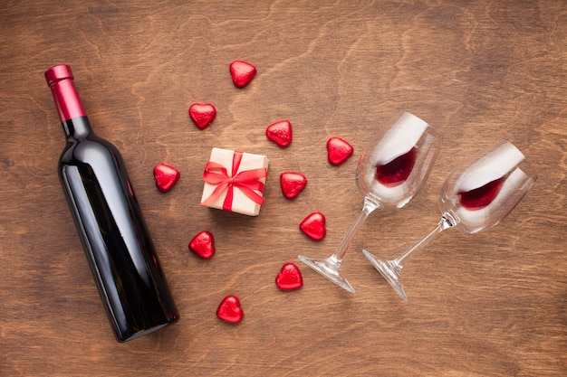 Flat lay decoration with heart shaped candies and wine