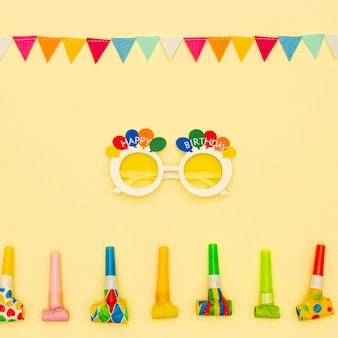 Flat lay decoration with party glasses and blowers