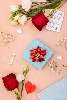 Flat lay decoration with present box and roses
