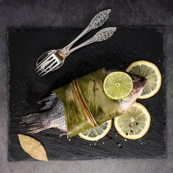 Flat lay decoration with tasty fish and lemons