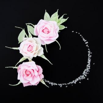 Flat lay decorative floral frame on black background
