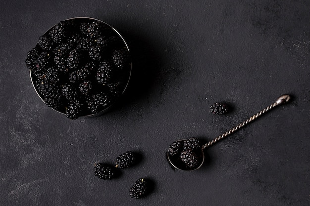 Flat lay delicious blackberries in minimalist bowl