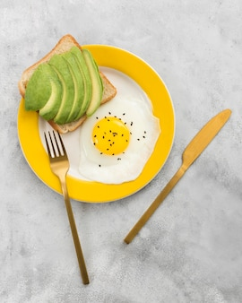 Flat lay of delicious breakfast with avocado