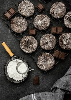 Flat lay of delicious chocolate cookies with powdered sugar