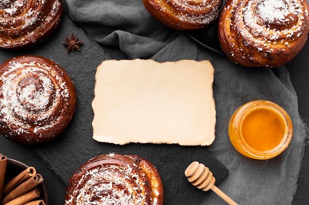 Lay piatto di deliziosi panini alla cannella con copia spazio