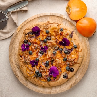 Flat lay of delicious cooked pizza with persimmons and flower petals