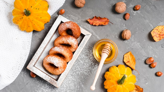 Flat lay of delicious donuts and honey