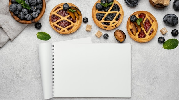 Flat lay of delicious fruit pies with notebook
