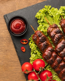 Flat lay of delicious kebab on slate with ketchup and salad