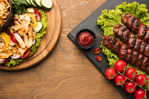 Flat lay of delicious kebab on slate with other dishes and ketchup