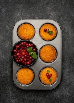 Flat lay of delicious muffins with berries in pan