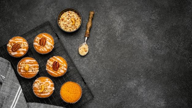 Lay piatto di deliziosi muffin con noci e spazio di copia