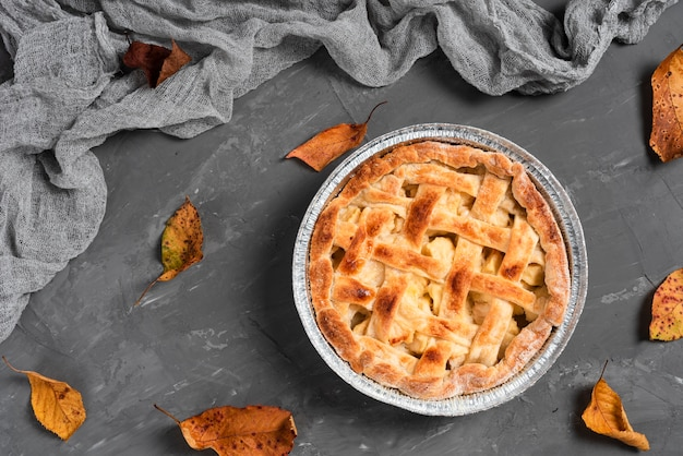 Flat lay of delicious pie surrounded by leaves