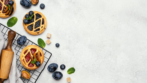 Lay piatto di deliziose torte con frutta e copia spazio