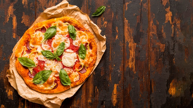Flat lay of delicious pizza concept on wooden table