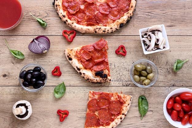 Плоская кладут вкусную пиццу на деревянный фон
