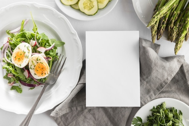 Flat lay delicious salad on a white plate with empty card