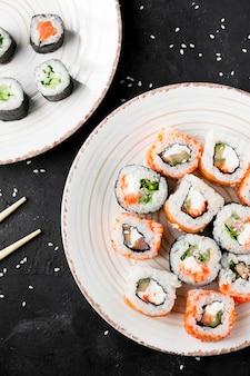 Плоские положите вкусные суши на тарелку