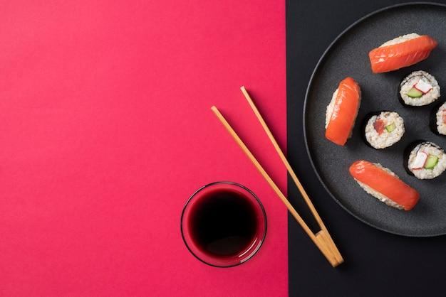 Плоские лежат вкусные суши на тарелке