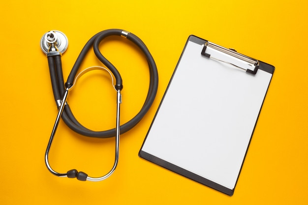 Flat lay design of stethoscope and blank clipboard pad with for medical concept.