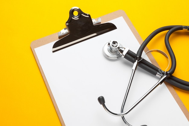 Flat lay design of stethoscope and blank clipboard pad