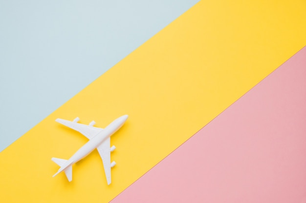 Flat lay design of travel concept with plane and cloud on blue, yellow and pink