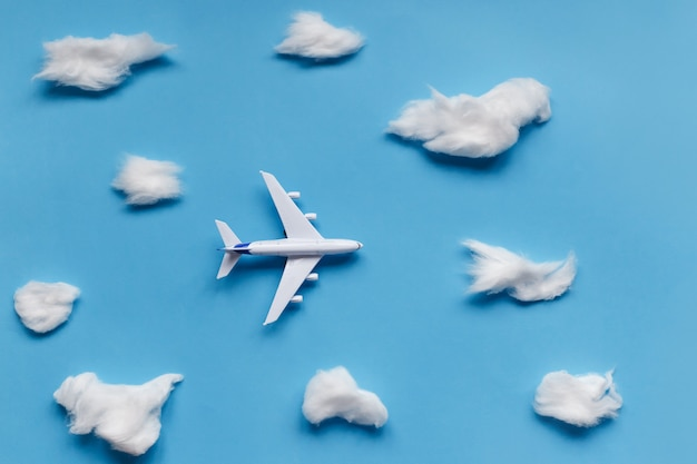 Flat lay design of travel concept with plane and cloud on blue
