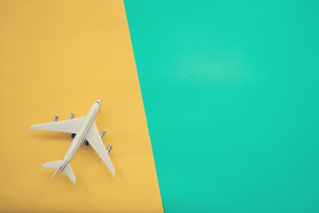 Flat lay design of travel concept with plane on green and yellow background