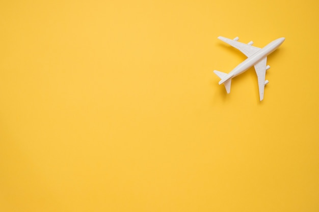 Flat lay design of travel concept with plane on yellow