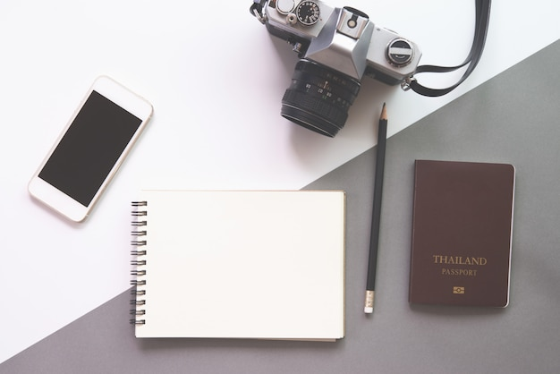 Flat lay design of work desk with notebook, glasses, camera, smartphone and passport on white background.