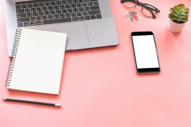 Flat lay design of workspace desk with laptop, blank notebook, smartphone, pencil, stationery