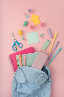 Flat lay desk arrangement with backpack