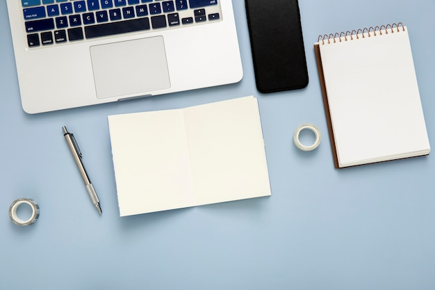Flat lay desk arrangement with empty notepad on blue background