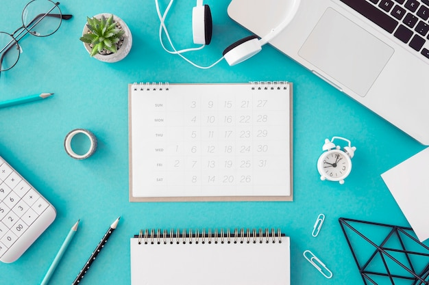 Flat lay desk calendar on blue background