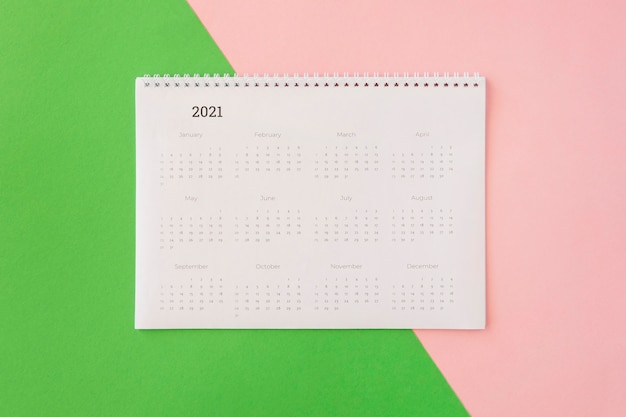 Flat lay desk calendar on coloured background
