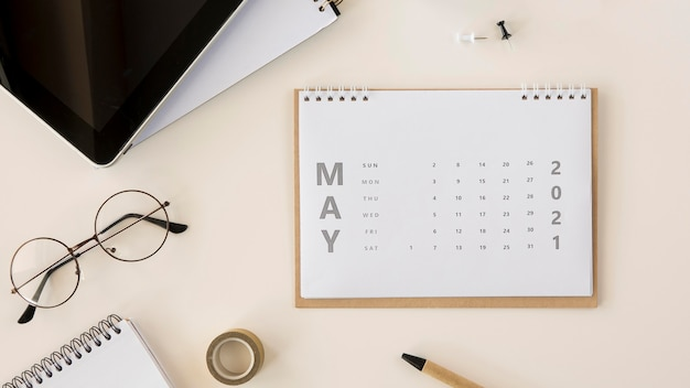 Flat lay desk calendar and reading glasses
