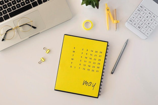 Flat lay desk calendar with laptop and reading glasses