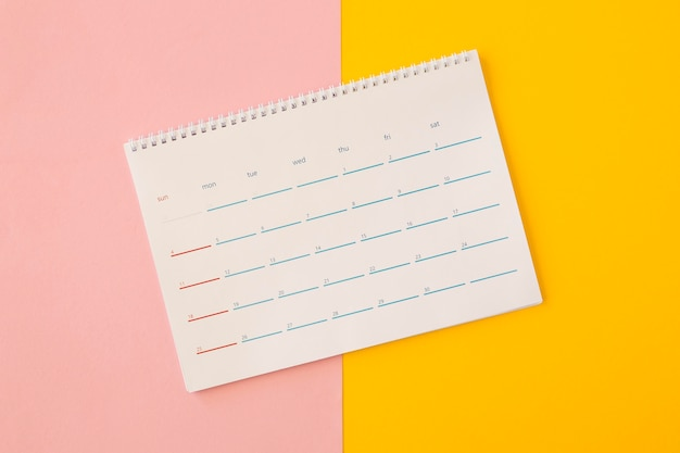 Flat lay desk calendar on yellow and pink background