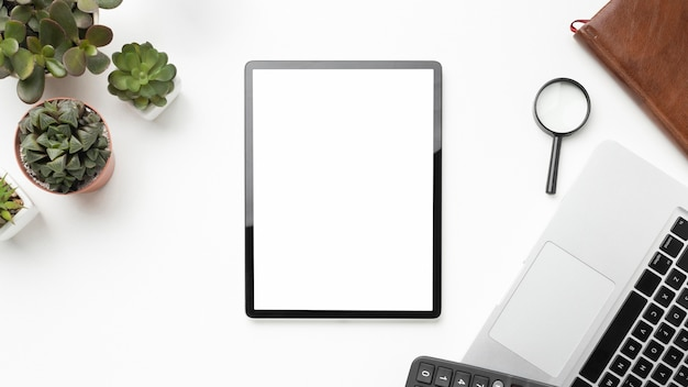 Flat lay desk elements arrangement with empty screen tablet