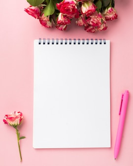 Flat lay of desk with bouquet of roses and notebook