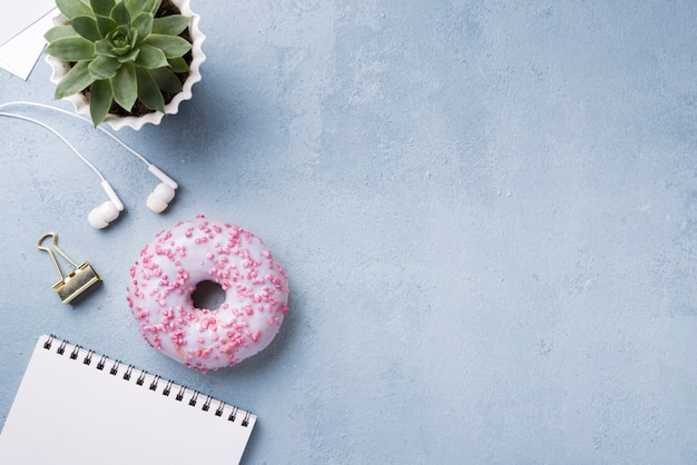 Flat lay of desk with doughnut and notebook