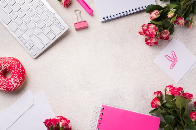 Flat lay of desk with keyboard and bouquet of roses