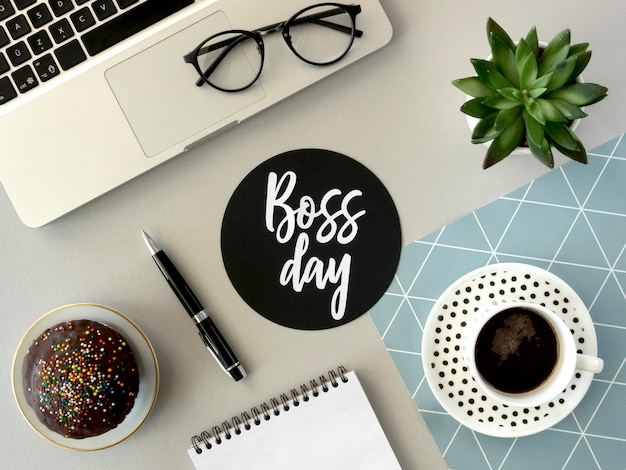 Flat lay desk with sign for boss day