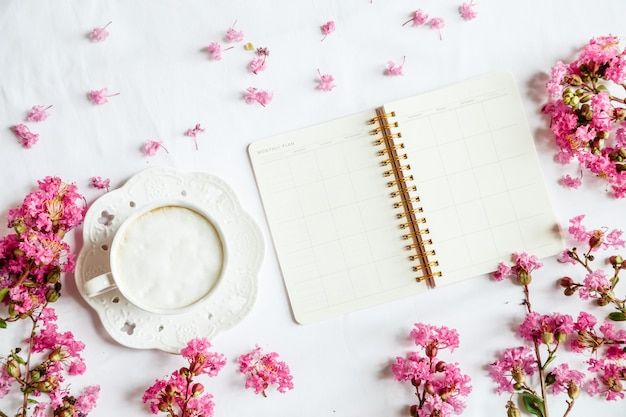 Flat lay desktop items: coffee mug, notebook and pink flowers on white table