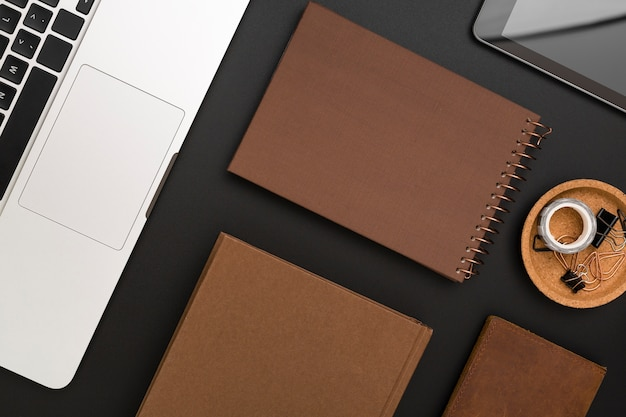 Flat lay of desktop with agendas and laptop