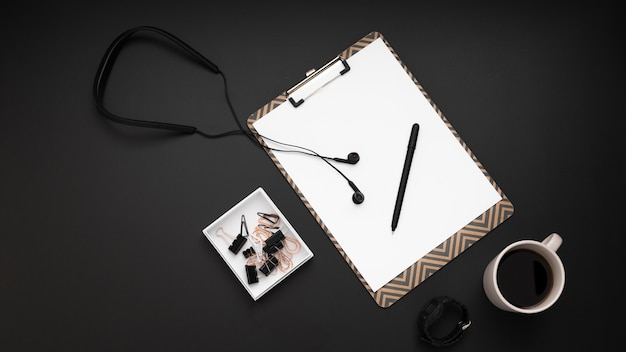 Flat lay of desktop with headphones and notepad